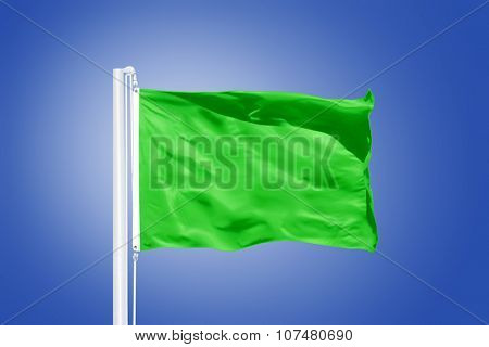 Green flag flying in a stiff breeze against clear blue sky.