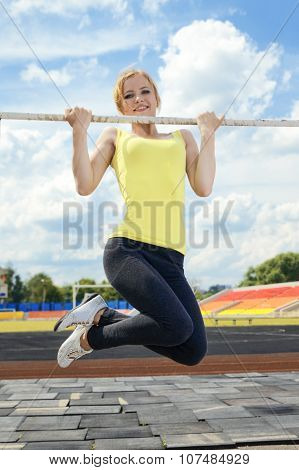 Young athletic woman holding on to horizontal bar