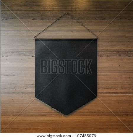 Black pennant hanging on the wall at wooden background. 3d render