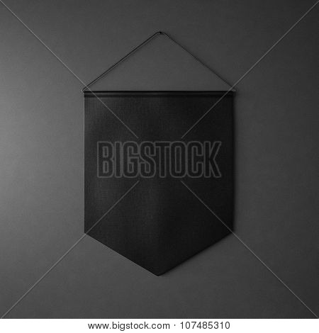 Black pennant hanging on wall at black background. 3d render
