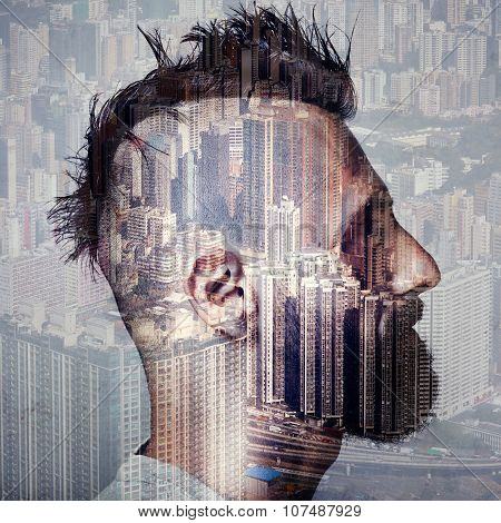 Double exposure portrait of man with mohawk and a city