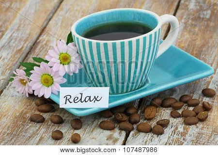 Word relax with cup of coffee and pink daisy flowers