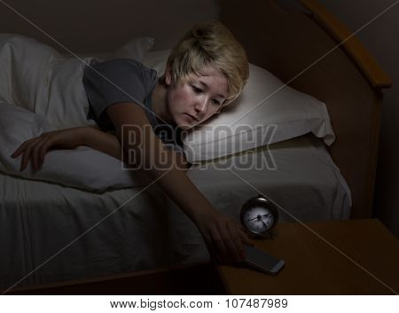 Teen Girl Checking Cell Phone Late At Night While In Bed
