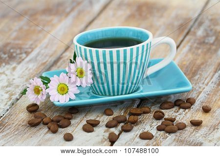 Coffee in vintage cup and pink daisy flowers on rustic wooden surface with copy space