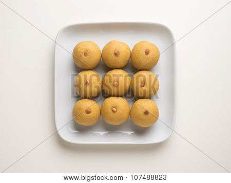 Ladu- An Indian sweet neatly arranged on a white contemporary plate. Shot from above.