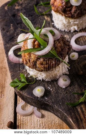board burgers on bread with onion and herbs