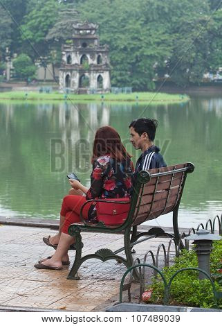 Asian couple resting on wooden benches