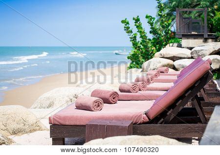 Wrapped Towels With Empty Sunbed On A Beautiful Beach