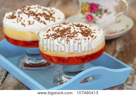 Traditional strawberry trifle dessert with fresh whipped cream and sprinkled with chocolate on woode