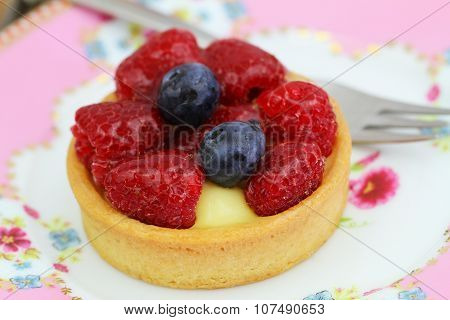 Delicious crunchy tartelette with custard, fresh raspberries and blueberries, closeup
