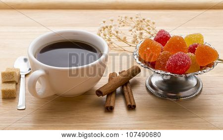 Fresh cup of hot tea, colorful marmalade, brown sugar cane cubes and cinnamon sticks.