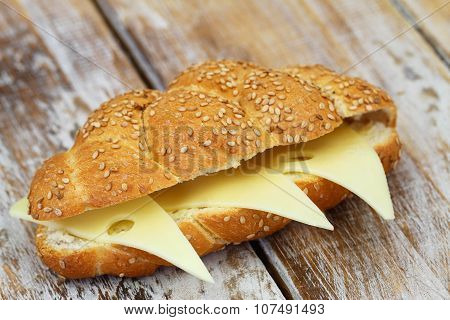 Crunchy sesame seeds bread roll with Swiss cheese on rustic wooden surface