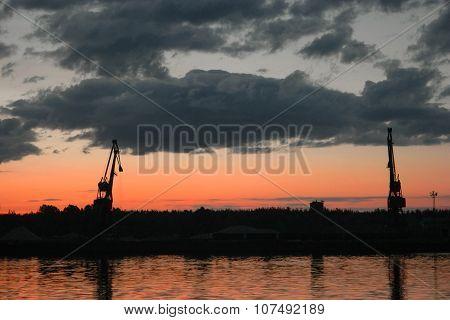 Sunrise over Volga-river and port cranes on sky