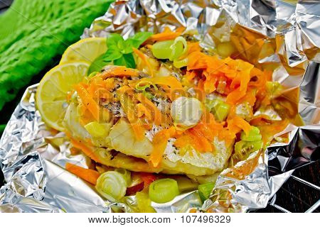 Pike with carrots and leeks in foil on dark board