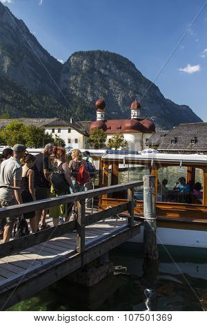KOENIGSSEE, GERMANY - AUGUST 13, 2015: Boat at the landing stage of the Koenigssee near Berchtesgaden in Bavaria with the Church of St. Bartholomew in the background