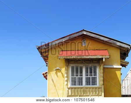 Yellow house on blue sky