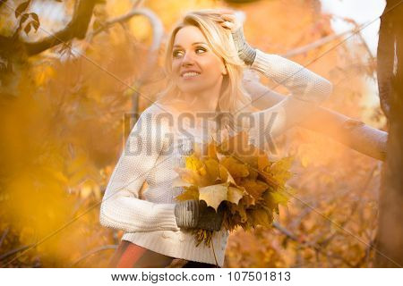 Blond woman with bouquet from maple leaves