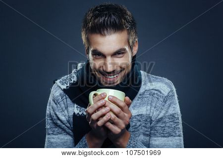 Young Man Is Freezing And Holding Cup Of Tea