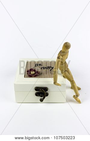Wooden Puppet Sitting On A Jewellery Box
