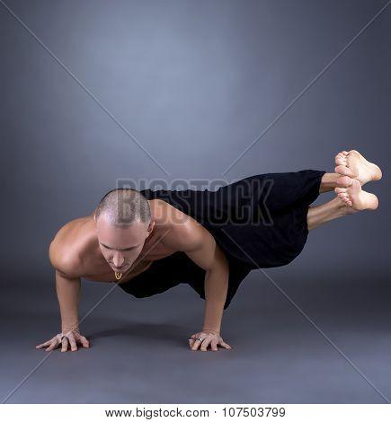 Studio photo of middle-aged man practicing yoga