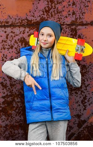 Smiling girl holding color plastic penny board or skateboards outdoor and showing Ok