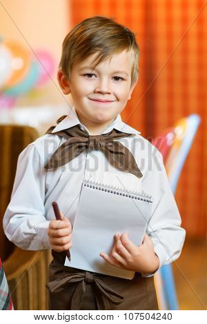 Happy cute boy waiter in apron writing order and looking at camera