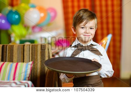 Happy cute little boy smiling waiter holding a tray