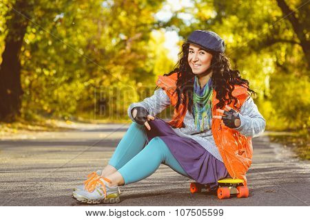 Smiling woman sitting on color plastic penny board or skateboard outdoor