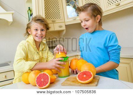 Children with citrus. Boys squeezing fresh orange juice