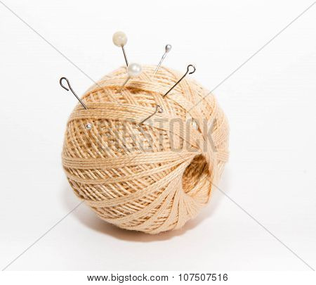Ball Of Threads With The Thrust Pins On A White Background