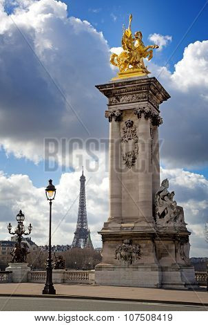 Column with gilded sculpture on the Pont Alexandre III bridge with the Eiffel Tower in the background. Paris, France.