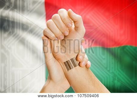Barcode Id Number On Wrist And National Flag On Background - Madagascar