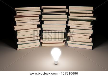 Three Piles Of Book With Glowing Lightbulb In The Middle