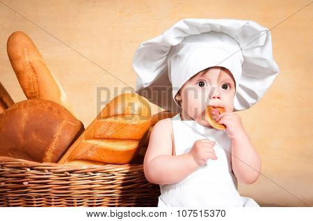 Little Cook In A Chef's Hat Eating A Bagel. Close-up Portrait.
