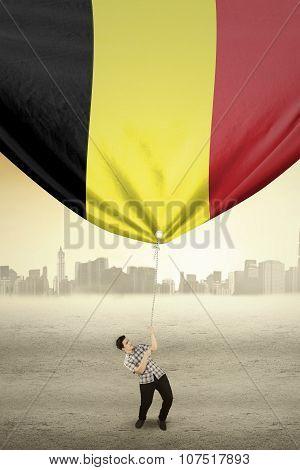 Man Dragging Flag Of Belgium