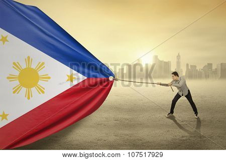 Man Dragging Flag Of Philippines