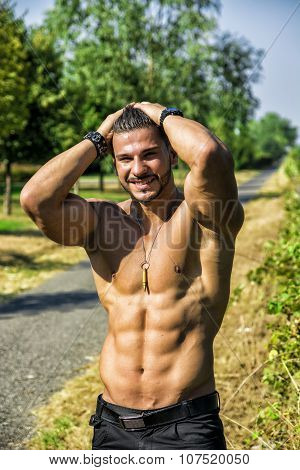 Shirtless bodybuilder showing muscles, smiling outdoor