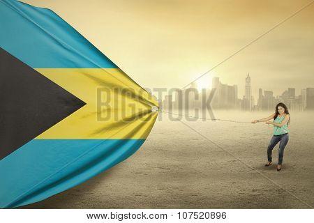Woman Pulling Flag Of Bahamas