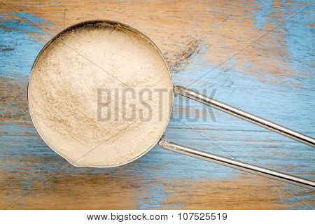 metal measuring scoop of African baobab fruit powder against painted wood background