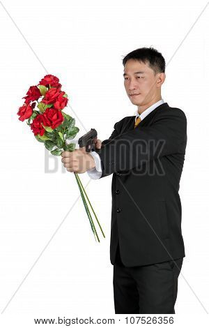 Asian Businessman Standing With Holding A Bouquet Of Rose Flowers And Gun, Isolated On White