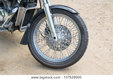 Close up front wheel motorcycle chopper  on the floor.