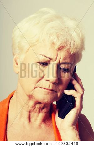 An old lady talking through phone.She is receiving bad news.