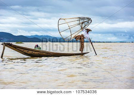Intha Fisherman Fishing In His  Canoe With Fishing Net