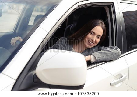 joyful young woman driving a car and looking at rearview mirror