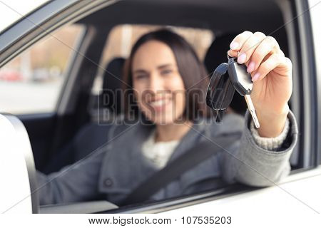 smiley woman sitting in car and showing the car keys. focus on the keys