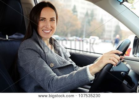 smiley beautiful woman driving a car and looking at camera