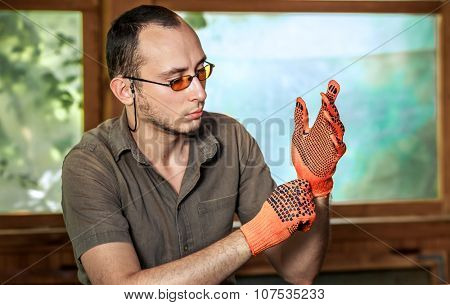 Young man in glasses wearing protective gloves