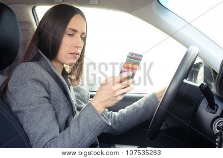 serious young woman driving a car and looking at her smartphone