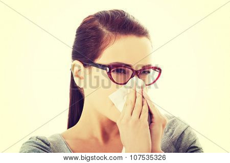 Young casual woman in eyeglasses blowing her nose.