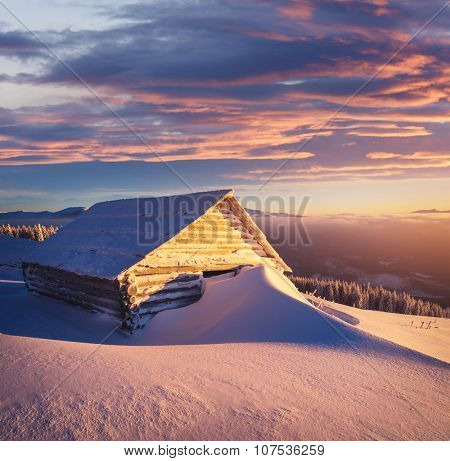 Winter landscape with wooden huts in the mountains. Sunny morning. Big snowdrift